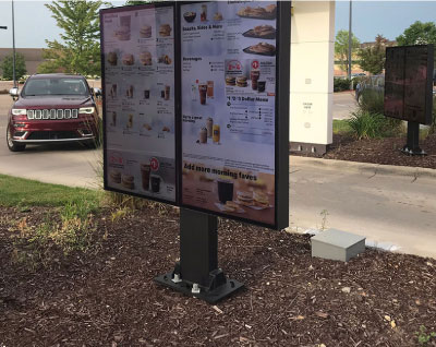 Outdoor digital menu board at quick services restaurant with car driving up to order